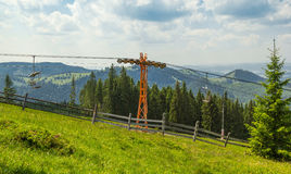 Empty chairlift in ski resort with green grass and blue sky Royalty Free Stock Photo