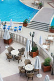 Empty chairs by the beautiful resort pool Royalty Free Stock Photos