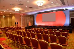 Empty chairs in conference room. Conference room with rows of empty chairs and stage with screen Royalty Free Stock Photos