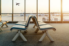 Empty chairs in the departure hall at airport with airplane taki Stock Images
