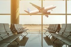 Empty chairs in the departure hall at airport on background of airplane taking off at sunset. Travel concept.  stock image