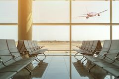 Empty chairs in the departure hall at airport on background of airplane taking off at sunset. Travel concept.  royalty free stock photo
