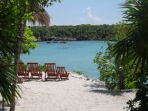 Empty chairs in front of a lagoon. Empty chairs on the sand in front of a blue lagoon, surrounded by tropical vegetation. Xel-Ha Park, Mayan Riviera, Mexico Royalty Free Stock Photo