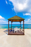 Empty chairs and gazebo by the beach. Stock Photos