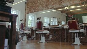 Old fashioned interior of a hair salon. Empty chairs and mirrors in barber shop. Old fashioned interior of a hair salon stock video footage