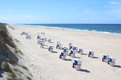 Empty chairs on sandy beach