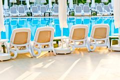 Empty chairs stand around the pool at the hotel Stock Image