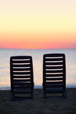Empty chairs stand on sand near sea Stock Photos