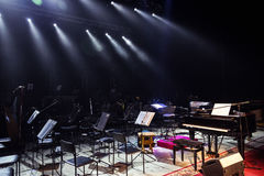 Empty chairs stand on stage in Concert Hall. Piano on stage. Sce Stock Photos