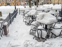 Outdoors restaurant chairs and tables covered with thick snow cover. Empty chairs and tables covered with heavy snow cover outside restaurant Royalty Free Stock Photography
