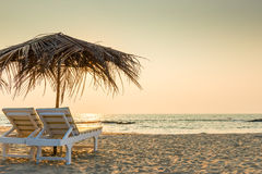 Empty chairs under thatched umbrellas Royalty Free Stock Photography