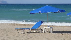 Empty Chaise Longue Under Sun Umbrella on the Ocean Coast. Summer vacation scene. Empty chaise longues under sun umbrella on the ocean coast. Beach with white stock video