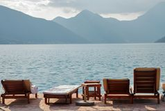 Empty chaise lounges against the background of the sea landscape. Empty deck chairs on the background of the sea landscape. Frontal image with deck chairs on the stock images