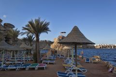 Empty chaise lounges and awnings on the beach. Coast of the Red Sea Royalty Free Stock Images