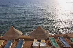 Empty chaise lounges and awnings on the beach. Coast of the Red Sea Stock Photos