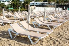Empty chaise-lounges on the beach in the city of Costa Teguise. Island Lanzarote, Spain stock images