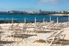 Empty chaise-lounges on the beach in the city of Costa Teguise. Island Lanzarote, Spain stock photos