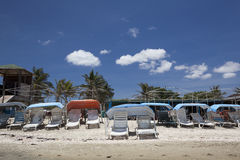 Empty beach at noon. Empty chaise lounges on a deserted beach Royalty Free Stock Images