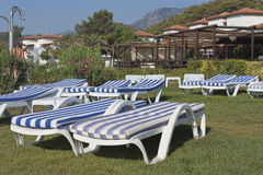 Empty chaise lounges with mattresses on the lawn at the hotel in. CAMYUVA, KEMER, TURKEY - JULY 14, 2015: Empty chaise lounges with mattresses on the lawn at the royalty free stock photo