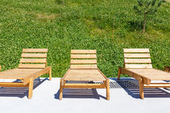 Empty chaise lounges situated on concrete floor. Three empty wooden chaise lounges situated on concrete floor near grassy hill. Summer mounting vacation stock photos