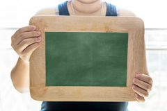 Empty Chalk board Background/Blank.Blackboard Background.Blackboard texture. Chalkboard or School board holded by girl hand use for background ,backdrop Royalty Free Stock Photos