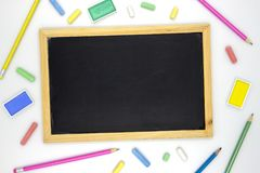 Empty chalkboard with art supplies on white background. Blackboard and colorful chalk flat lay photo.