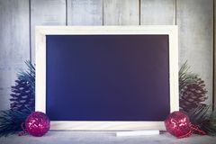 Empty chalkboard with christmas decoration on a wooden backgroun Royalty Free Stock Photo