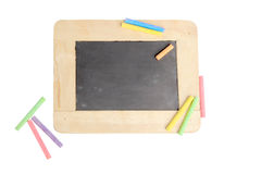 Empty chalkboard for copy space with colorful pieces of chalk on white background Royalty Free Stock Images