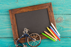 empty chalkboard with copyspace and colorful crayons on wooden table Royalty Free Stock Images