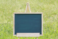 Empty chalkboard with easel. Empty chalkboard with wooden easel on green field background Stock Photography