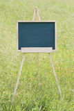 Empty chalkboard with easel. Empty chalkboard with wooden easel on green field background Stock Images