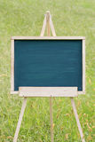 Empty chalkboard with easel. Empty chalkboard with wooden easel on green field background Royalty Free Stock Images