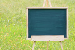 Empty chalkboard with easel. Empty chalkboard with wooden easel on green field background Royalty Free Stock Photos