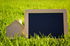 Empty chalkboard next to wooden small house Stock Images