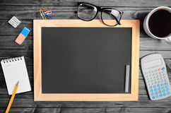 Empty chalkboard with office supply Royalty Free Stock Photo