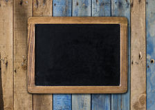 Empty chalkboard on wooden surface Royalty Free Stock Photography