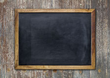 Empty chalkboard on wooden surface. Front view of a blank blackboard over a weathered wooden surface stock photography