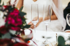 Empty chamagne wineglasses stand in the front of newlyweds Stock Photography