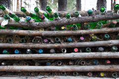 Empty Champagne Bottles Between Pine Logs Royalty Free Stock Photos