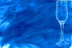 Empty champagne flute enveloped in blue smoke. stock photography