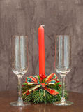 Empty champagne glasses on a background of red candles in a Christmas candlestick Royalty Free Stock Photo
