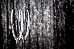 Empty champagne or wine glasses with glitter christmas tinsel decoration on background. royalty free stock image