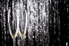 Empty champagne or wine glasses with glitter christmas tinsel decoration on background. stock image