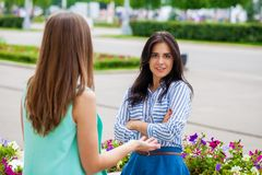 Empty chatter from which the head hurts. Two young women talking on the street royalty free stock photos