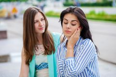 Empty chatter from which the head hurts. Two young women talking on the street royalty free stock image