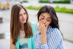 Empty chatter from which the head hurts. Two young women talking on the street stock photography