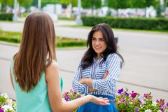 Empty chatter from which the head hurts. Two young women talking on the street royalty free stock images