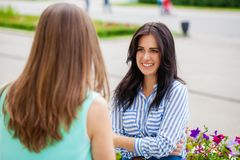 Empty chatter from which the head hurts. Two young women talking on the street stock photo