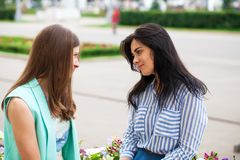 Empty chatter from which the head hurts. Two young women talking on the street royalty free stock photo