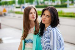 Empty chatter from which the head hurts. Two young women talking on the street royalty free stock photography